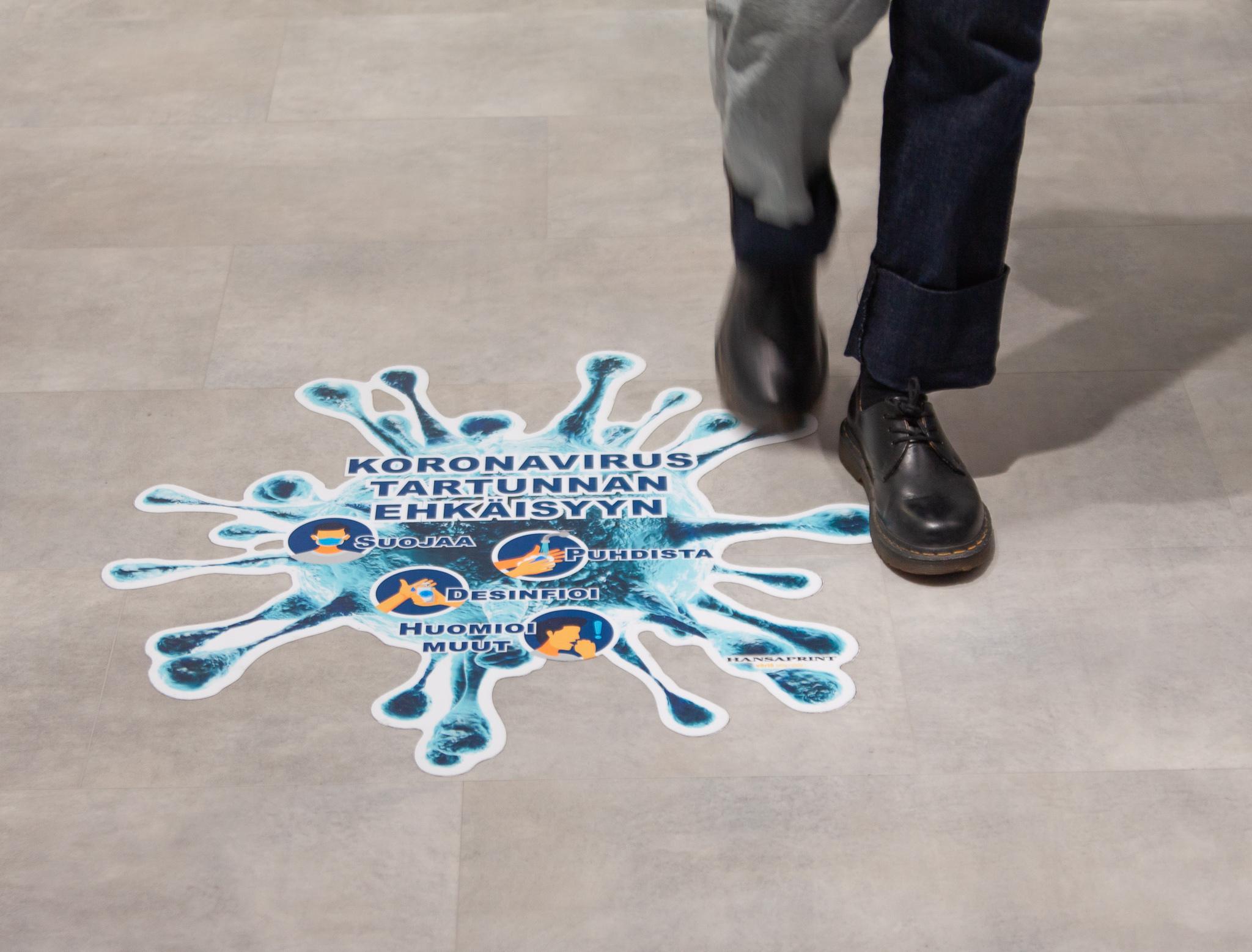 Kuvassa lattiatarrat ja jalat, jotka kävelevät ohi tarran.