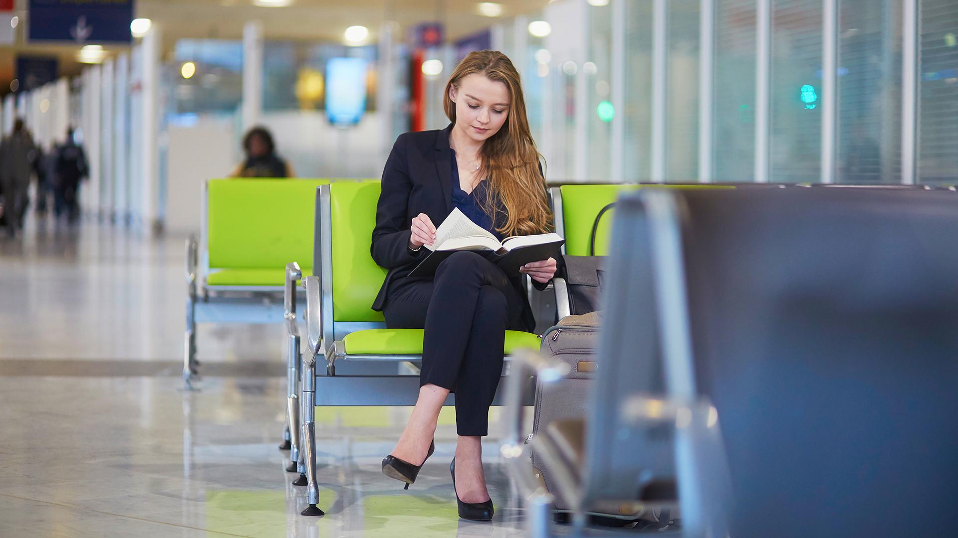 Nainen lukee kirjaa odotushallissa.
